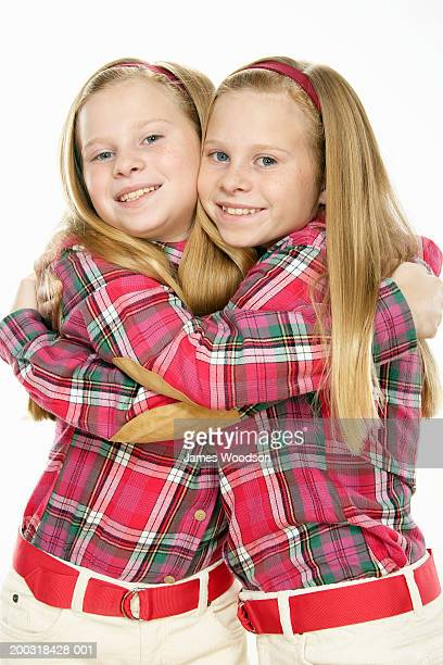 Twin girls (10-12) embracing, smiling, portrait
