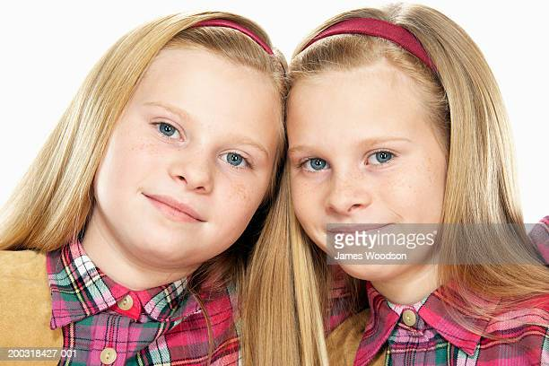 Twin girls (10-12) head to head, smiling, portrait, close-up