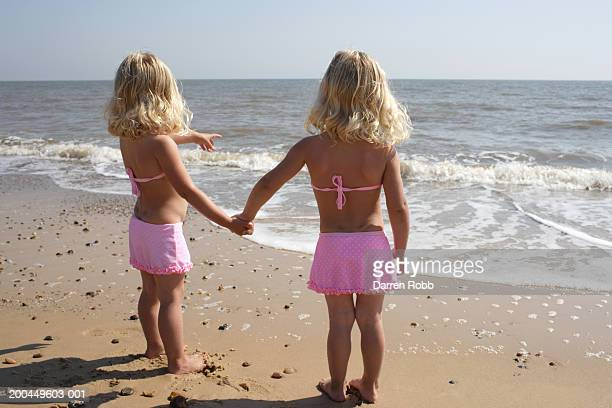 twin girls (2-4) holding hands on beach, one pointing, rear view - kids swimsuit models stock pictures, royalty-free photos & images