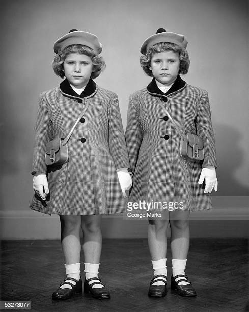 twin girls in hats & coats wearing white gloves - identical twin stock pictures, royalty-free photos & images