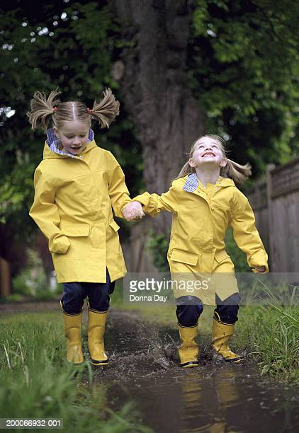 Twin girls (5-7) in raincoats and boots, jumping in mud puddle