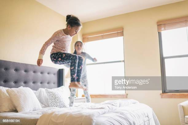 Twin girls jumping on parents bed