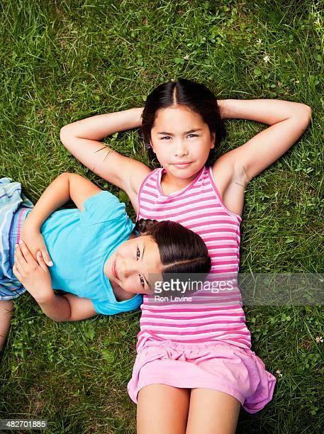 twin girls laying on the grass, portrait - ärmellos stock-fotos und bilder