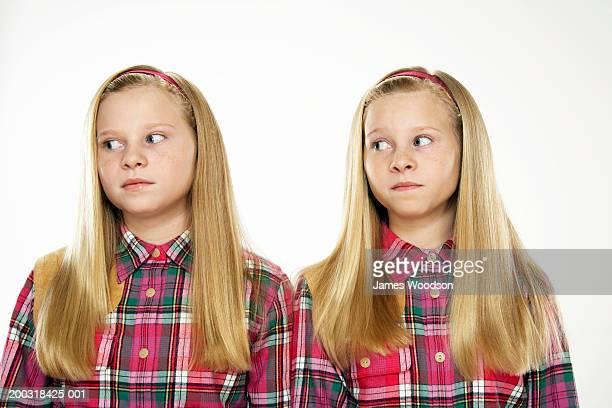 Twin girls (10-12) looking sideways, close-up