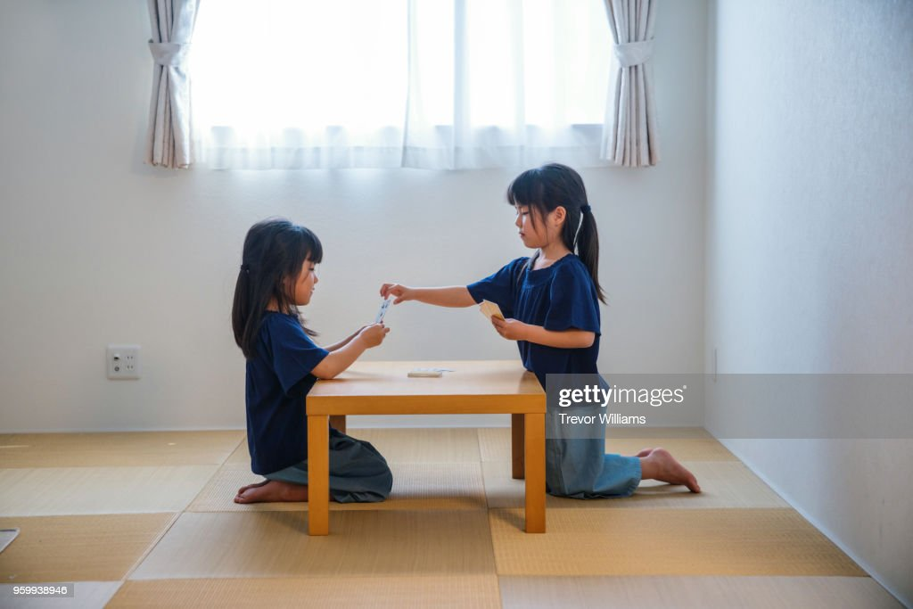Twin girls playing cards together : Stock-Foto