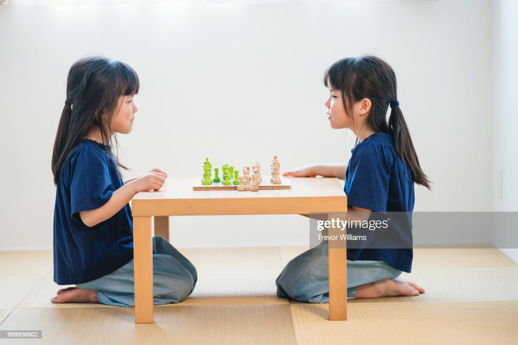 Twin girls playing chess together : Stock-Foto