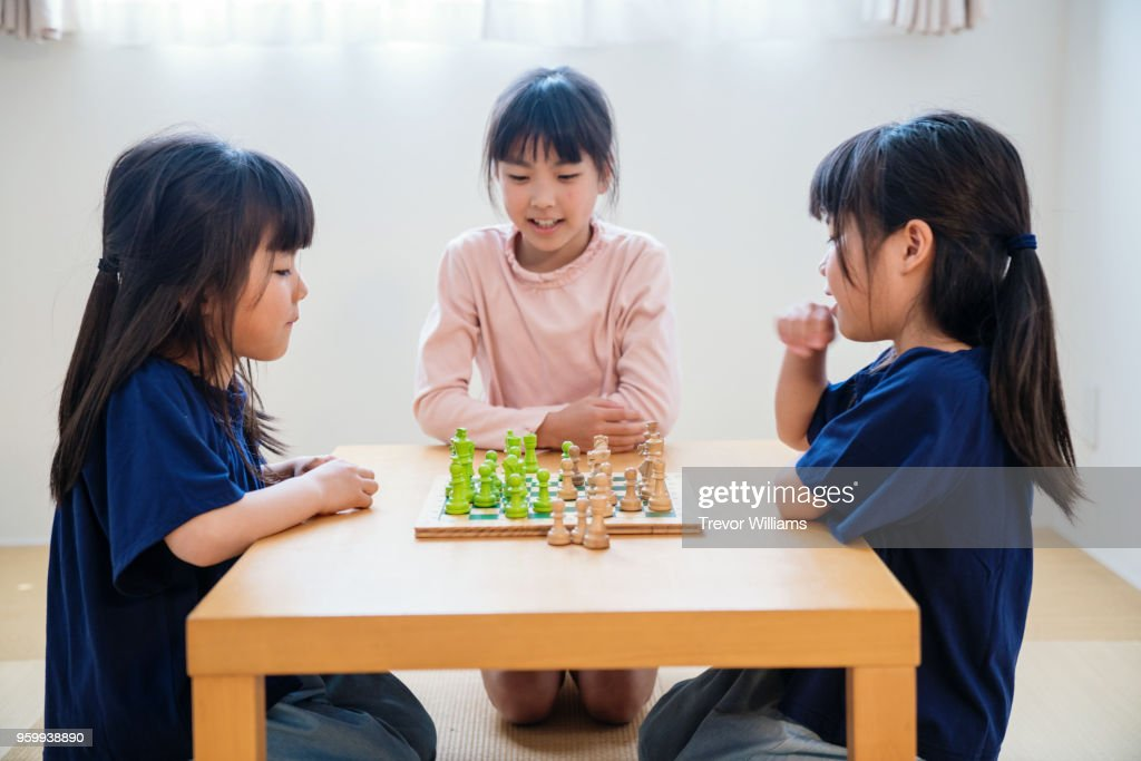 Twin girls playing chess together while older sister watches : Stock-Foto