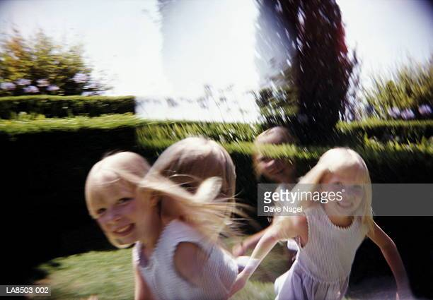 Twin girls (5-7) running outdoors, portrait (multiple exposure)