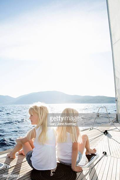 Twin girls sit on deck of yacht.