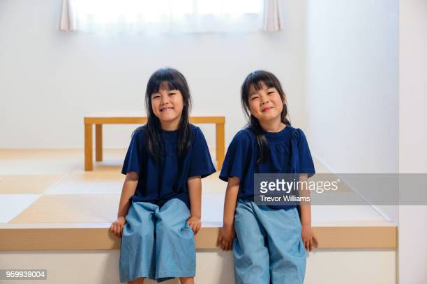 Twin girls sitting together in a living room