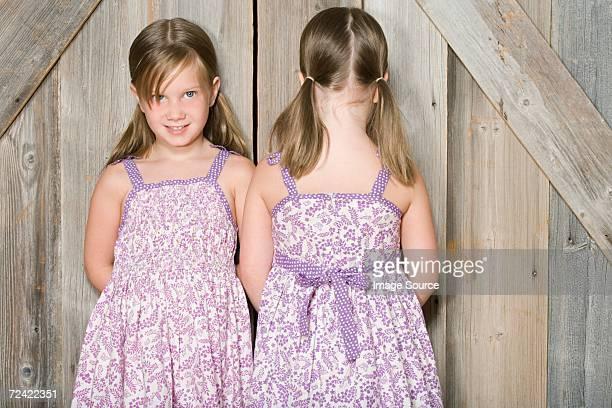 Twin girls standing against a door