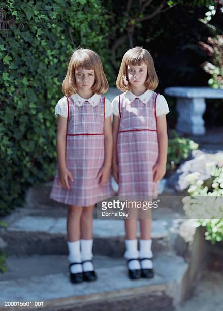Twin girls (4-6) standing side by side in garden, portrait