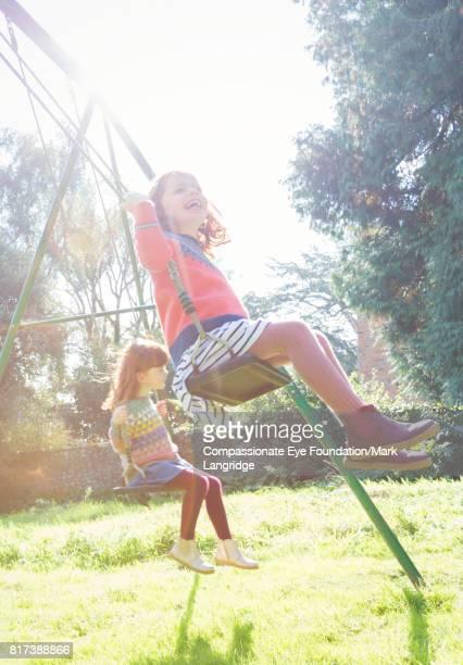 Twin girls swinging in sunny backyard