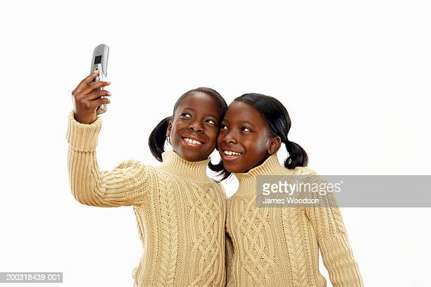 Twin girls (7-9) taking self portrait with camera phone, smiling