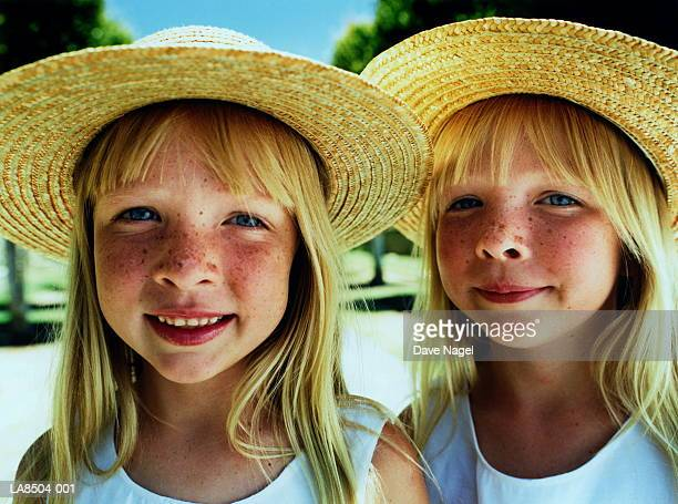 Twin girls (5-7) wearing straw hats, close-up, portrait