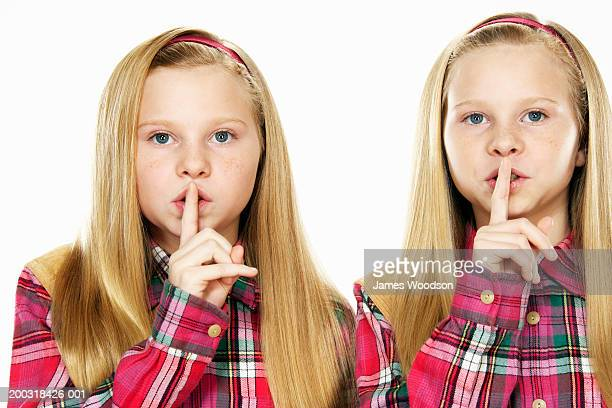 Twin girls (10-12) with fingers on lips, portrait, close-up