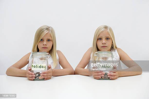 Twin girls with holiday and pension savings jars