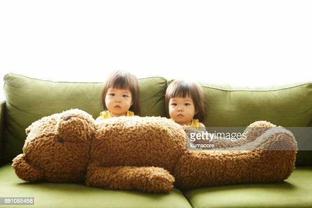 Twin little sisters and big teddy bear