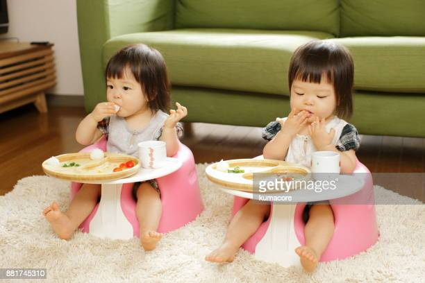 Twin little sisters eating a meal,close up