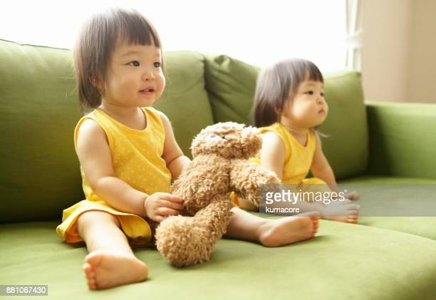 Twin little sisters playing with a teddy bear