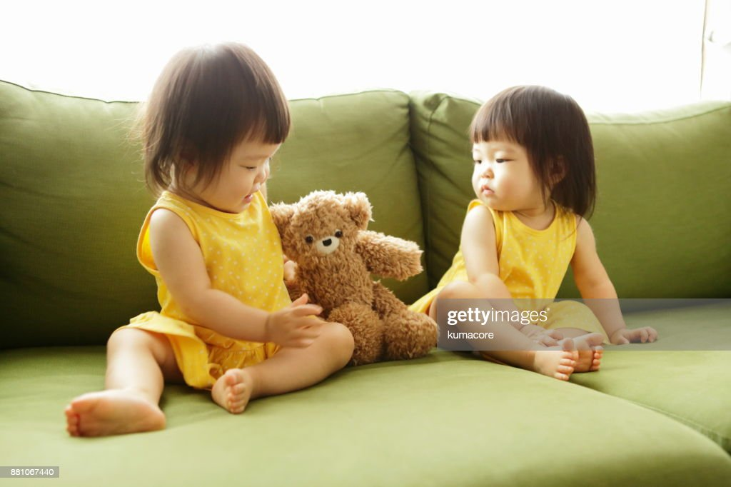 Twin little sisters playing with a teddy bear : Foto de stock