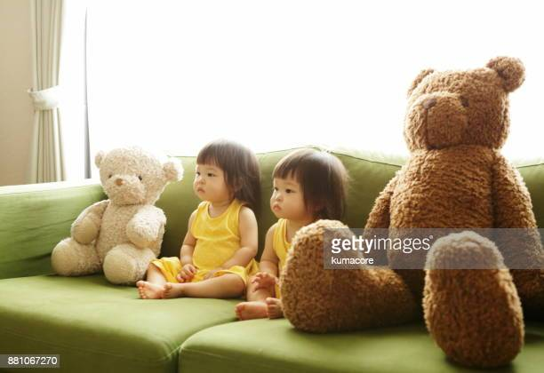 Twin little sisters sitting on sofa with teddy bear