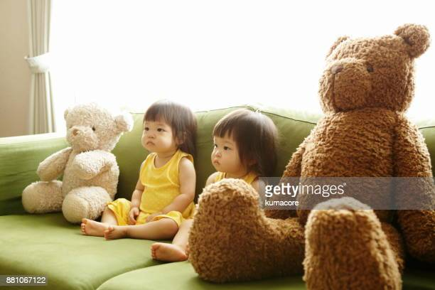 Twin little sisters sitting sofa with teddy bear