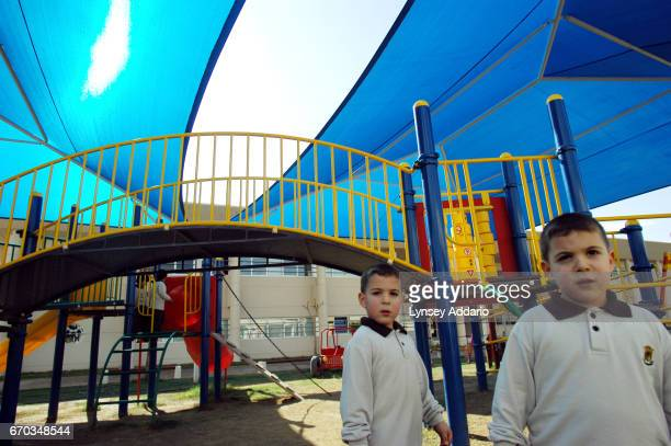 Twin Saudi boys play on the playground at the Kingdom school in Riyadh Saudi Arabia December 2003