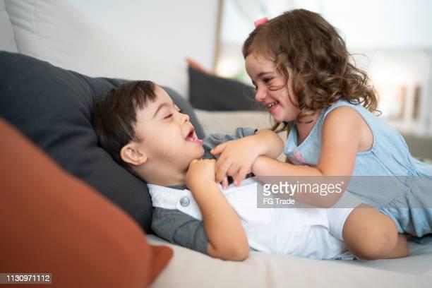 irmão gêmeo (síndrome de down e irmã) que cócegas no sofá - irmã - fotografias e filmes do acervo