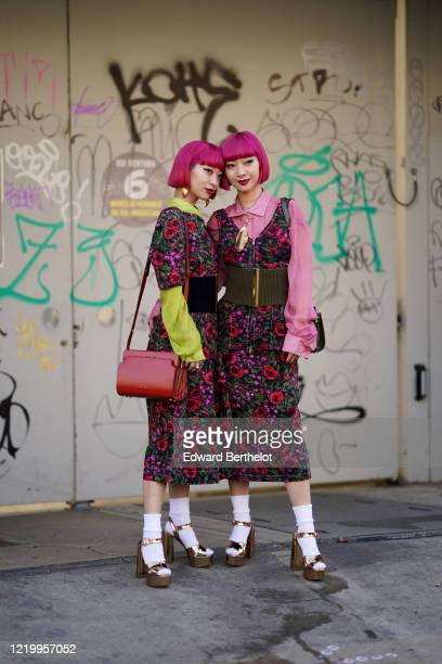 """Twin sisters Ami Suzuki and Aya Suzuki """"AmiAya"""" are seen and wear a floral print pink and red dress, a red leather bag, white socks, golden shiny..."""