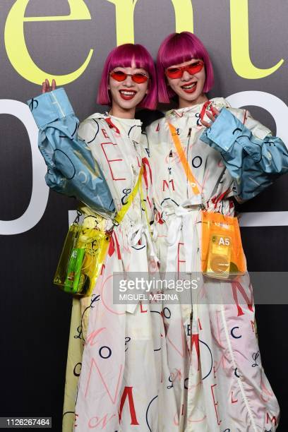 Twin sisters Ami Suzuki and Aya Suzuki of Japanese music duo Amiaya pose during a photo call as they arrive to attend the Moncler women's Fall/Winter...