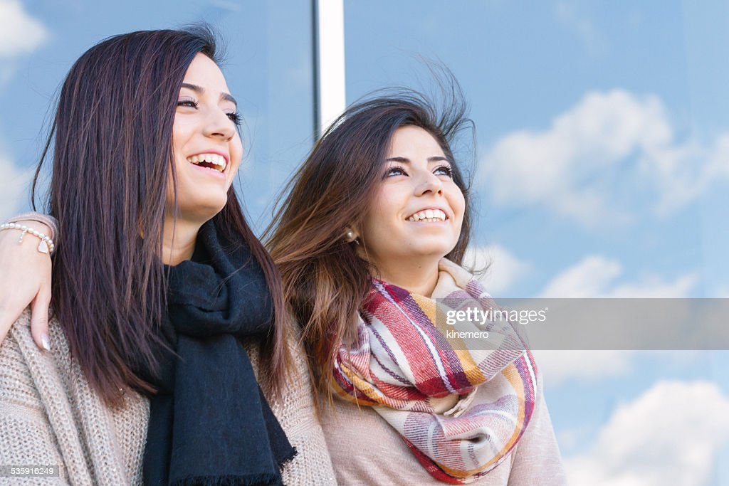 Twin sisters and friends happy with blue sky and clouds : Stock Photo