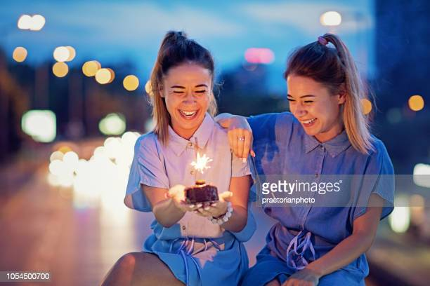 Twin sisters are celebrating their birthday with a cake and candle