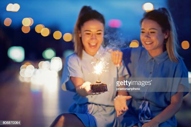twin sisters are celebrating their birthday with a cake and candle - happy birthday images for sister stock pictures, royalty-free photos & images