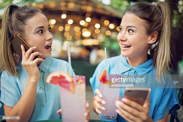 Twin sisters are drinking cocktails and talking with their friends using mobile phone