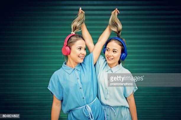 Zwillingsschwestern machen Spaß und ziehen ihre Pferdeschwänze einander bis die Musik hören