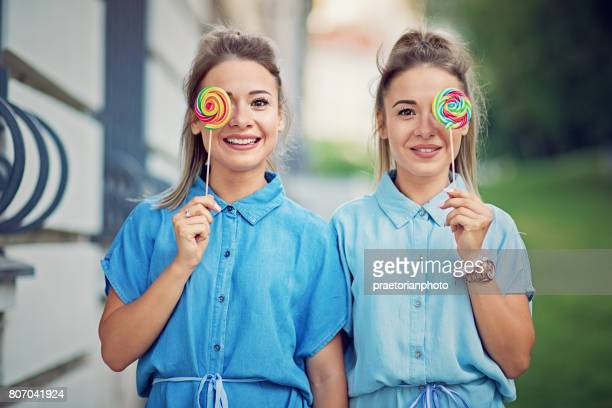 Twin sisters are making fun with colorful lollipops