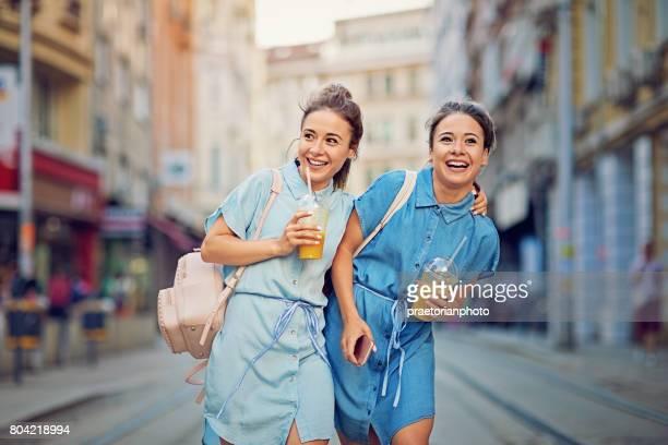 Zwillingsschwestern sind Fuß auf der Straße und machen Spaß