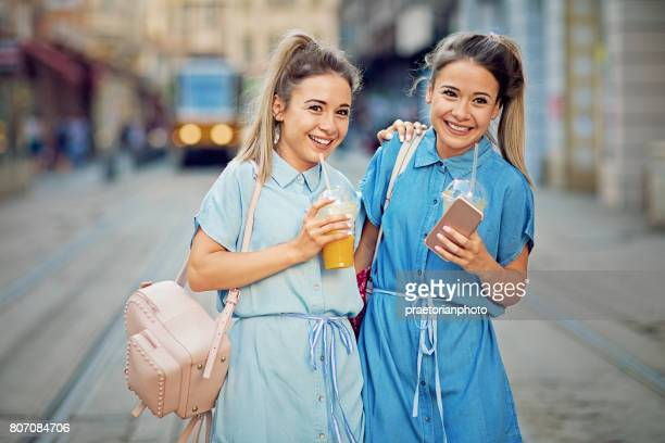 Twin sisters are walking on the street and make fun