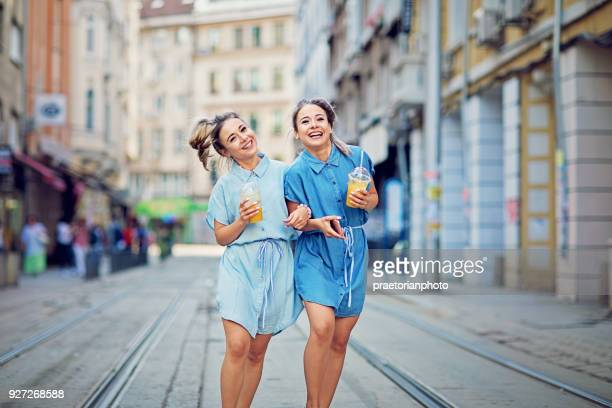 twin sisters are walking on the street and make fun - bulgarian girl stock photos and pictures
