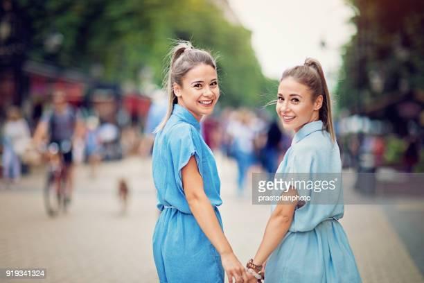 zwillingsschwestern sind auf der straße fuß. - schwester stock-fotos und bilder