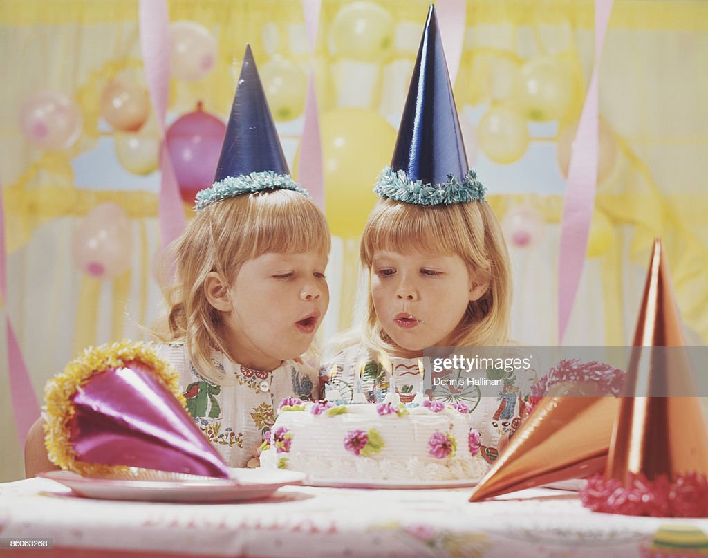 Twin Sisters Blowing Out Birthday Candles Stock Photo