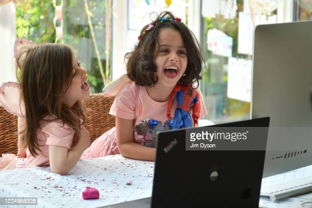 Twin sisters, daughters of the photographer, enjoy a Zoom party for their fourth birthday, on May 14, 2020 in Buckinghamshire, United Kingdom. The...