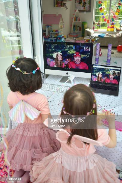 Twin sisters daughters of the photographer enjoy a Zoom party for their fourth birthday hosted by children's entertainers 'Party on a Cloud' on May...
