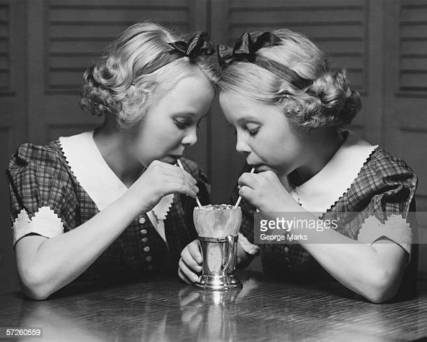 twin sisters (12-13) drinking through straws from same glass, (b&w) - identical twin stock pictures, royalty-free photos & images