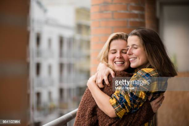 twin sisters embracing each other in balcony - sister stock pictures, royalty-free photos & images