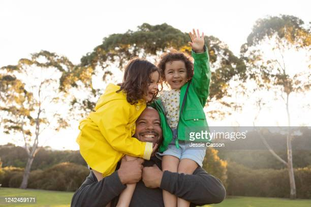 twin sisters have fun as father holds them on his shoulders - active lifestyle stock pictures, royalty-free photos & images