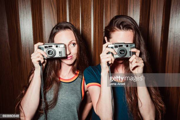 Twin Sisters Holding Cameras