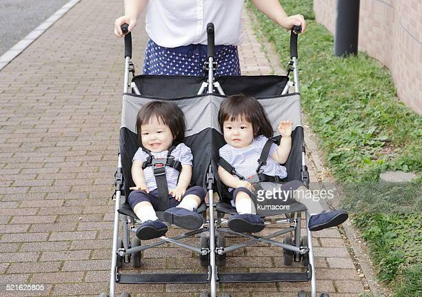 twin sisters in baby stroller. - asian twins stock photos and pictures