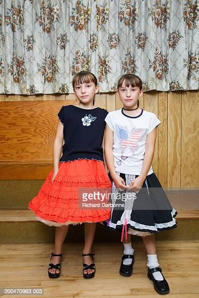 twin sisters (8-10) in square dancing attire standing side by side - tee reel bildbanksfoton och bilder